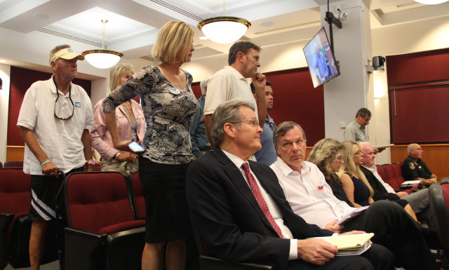 Members of the audience stand to show their opposition to the variance request. Seated in front of them are attorney William Merrill (far left) and the Allens. Rachel Hackney photo