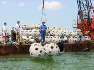 Crew members deploy reef balls into Sarasota Bay. Image courtesy SBEP