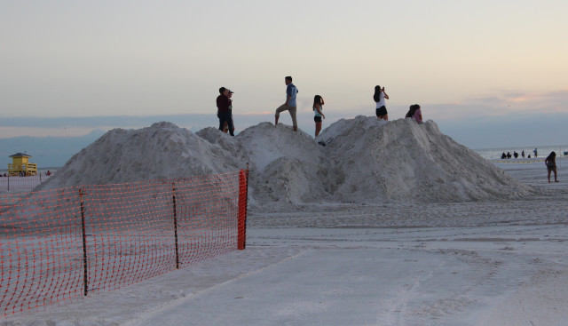 On Nov. 5, people stand atop piles of sand for the Crystal Classic sculptors as the sun sets on Siesta Key. Rachel Hackney photo
