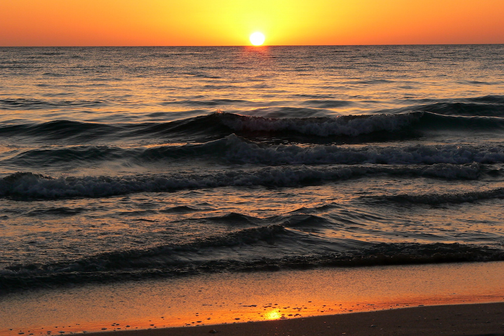Sol sinks beneath the waves at Siesta Key Beach.