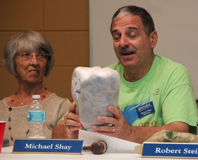 Joyce Kouba listens as Michael Shay explains her recycled milk jug idea. Rachel Hackney photo