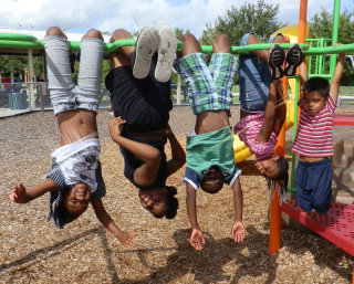Children hang from the monkey bars at Newtown Estates Park. Image courtesy Sarasota County