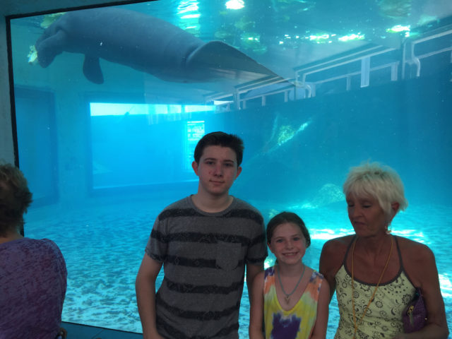 Skyler, Keylee and Michelle gather for a group photo with a manatee at Mote Aquarium. Photo courtesy of Steve Wall