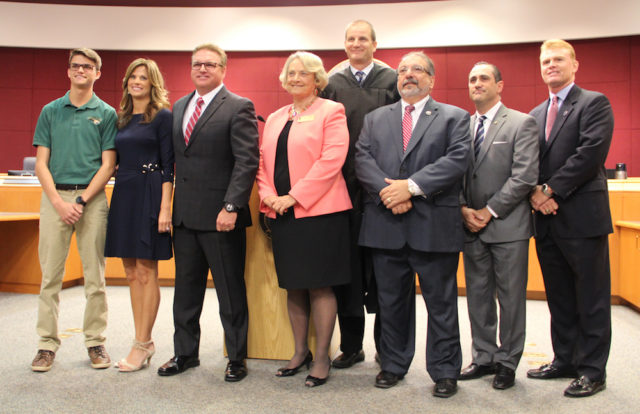 Following the ceremony, the commissioners all gather at the front of the chambers, along with Commissioner Mike Moran's son, Mikey (far left), and Moran's wife, Lori. Rachel Hackney photo