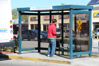 A SCAT rider awaits a bus at the Southgate Mall shelter. File photo