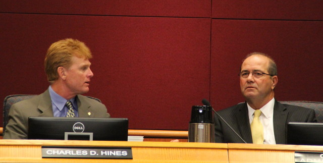 Commissioner Charles Hines talks with County Administrator Tom Harmer. File photo