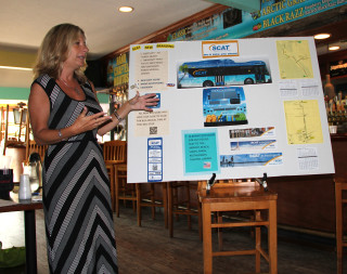 Kendra Keiderling shows Siesta Village Association members the 'wraps' for buses serving the island. File photo
