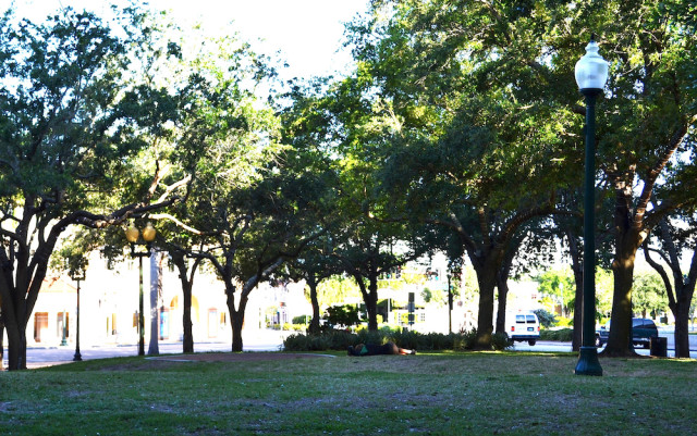 A homeless person sleeps on the ground in Five Points Park. File photo