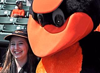Bird, the Orioles' mascot, greets a young reader at a previous game. Photo courtesy Sarasota County