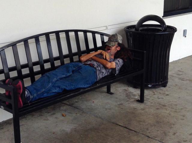 A homeless man sleeps on a bench outside City Hall. File photo