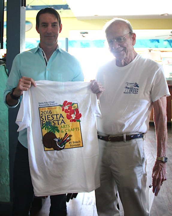 Russell Matthes (left) and Peter van Roekens hold up one of the 2016 Siesta Fiesta T-shirts that will be for sale this weekend. Rachel Hackney photo