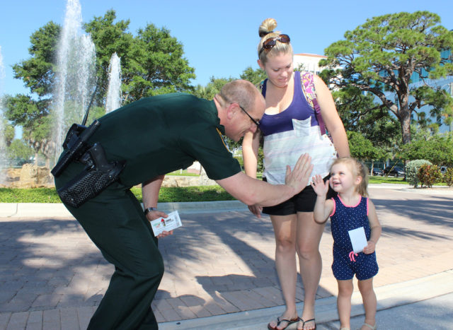 Lt. Brian Gregory rewards a youngster who has been practicing safety by giving her acoupon for a free Slurpee. Photo courtesy Sheriff's Office