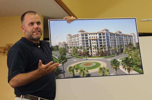 Todd Mathes, director of development for Benderson Development, holds up a rendering of a residential building for Siesta Promenade. File photo