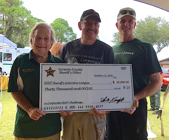 Sheriff's Activities League of Sarasota County Board members Stewie Bitterman (left) and Pete Abbot (right) accept a check for $30,000 from Col. Kurt A. Hoffman. Contributed photo