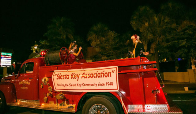 Catherine Luckner waves from the rear of the Siesta Key Association fire truck. Photo contributed by Peter van Roekens