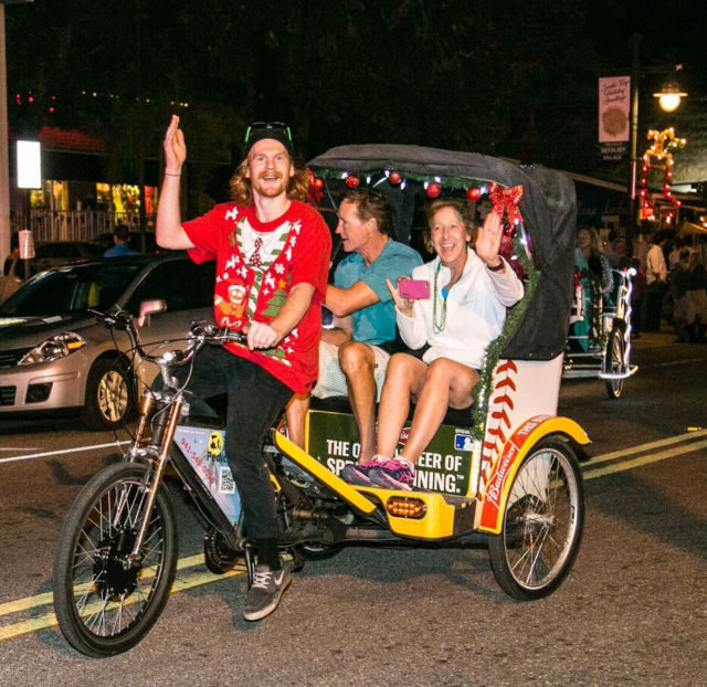 A Sun Ride Pedicab driver waves to onlookers. Photo contributed by Peter van Roekens