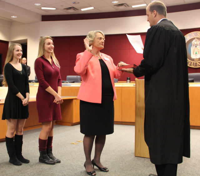 (From left) Lisa Detert and Stephanie Detert join their grandmother, Commissioner Nancy Detert, as she takes the oath of office administered by Judge Thomas Krug. Rachel Hackney photo